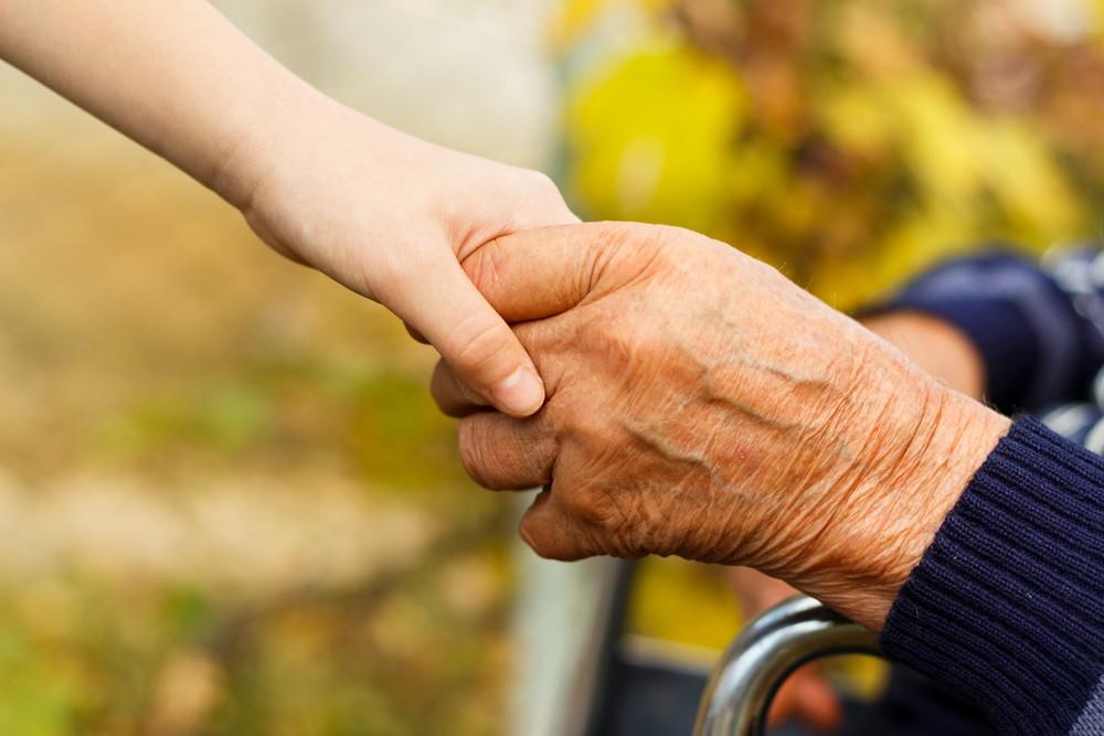 An elderly hand holds a child's hand.