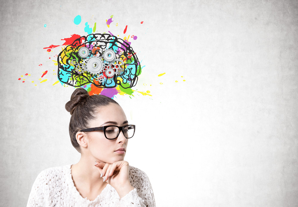 Woman sits thinking while a drawing of a colourful brain floats above her head