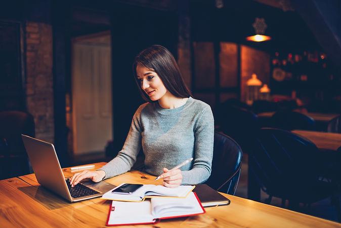 Brunette student watching webinar on lap