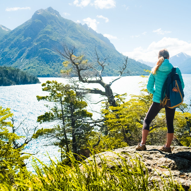 Woman hiker stands on the coast of the l