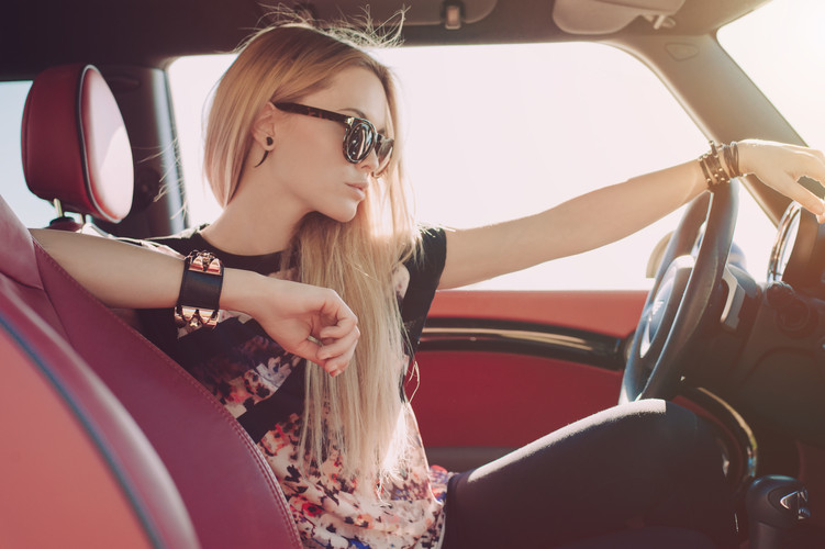 Blondie young girl at the wheel of sport