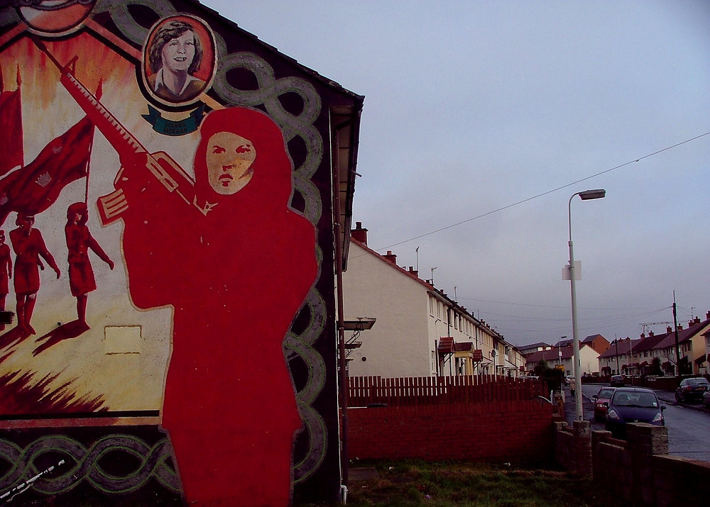 On the side of a builting, a stylized figure of a woman holding an automatic rifle is paints in red