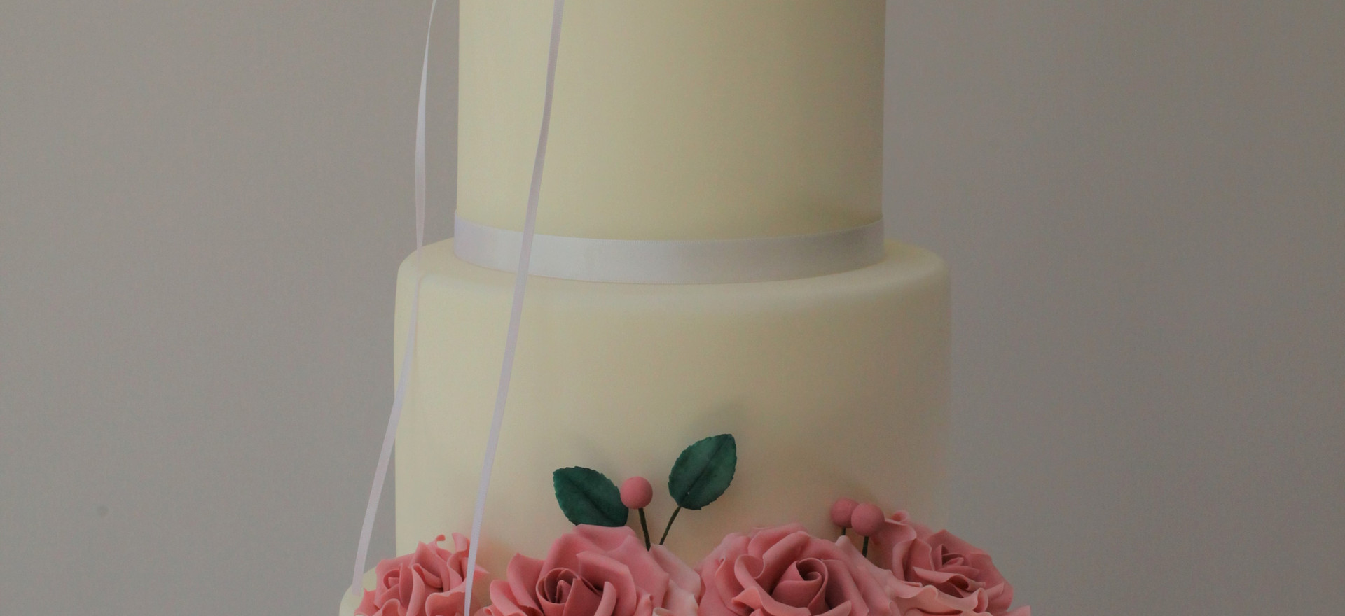 White iced cake with pink sugar roses