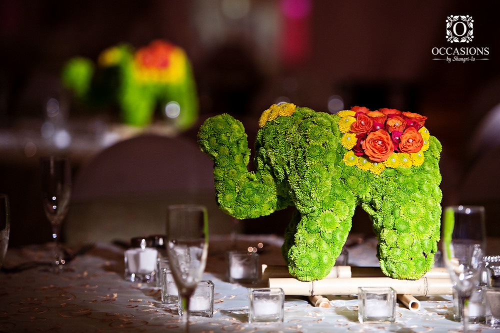 Medium Stuffed Elephant topiary with green, yellow, and red flower heads pinned into the stuffed elephant.