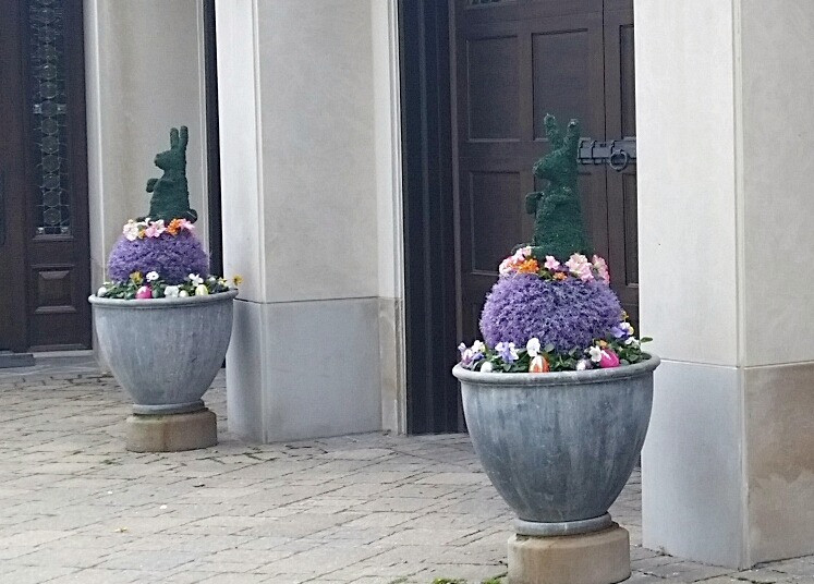 Two Standing Stuffed Bunnies colored green in planter pots with additional plants around them.