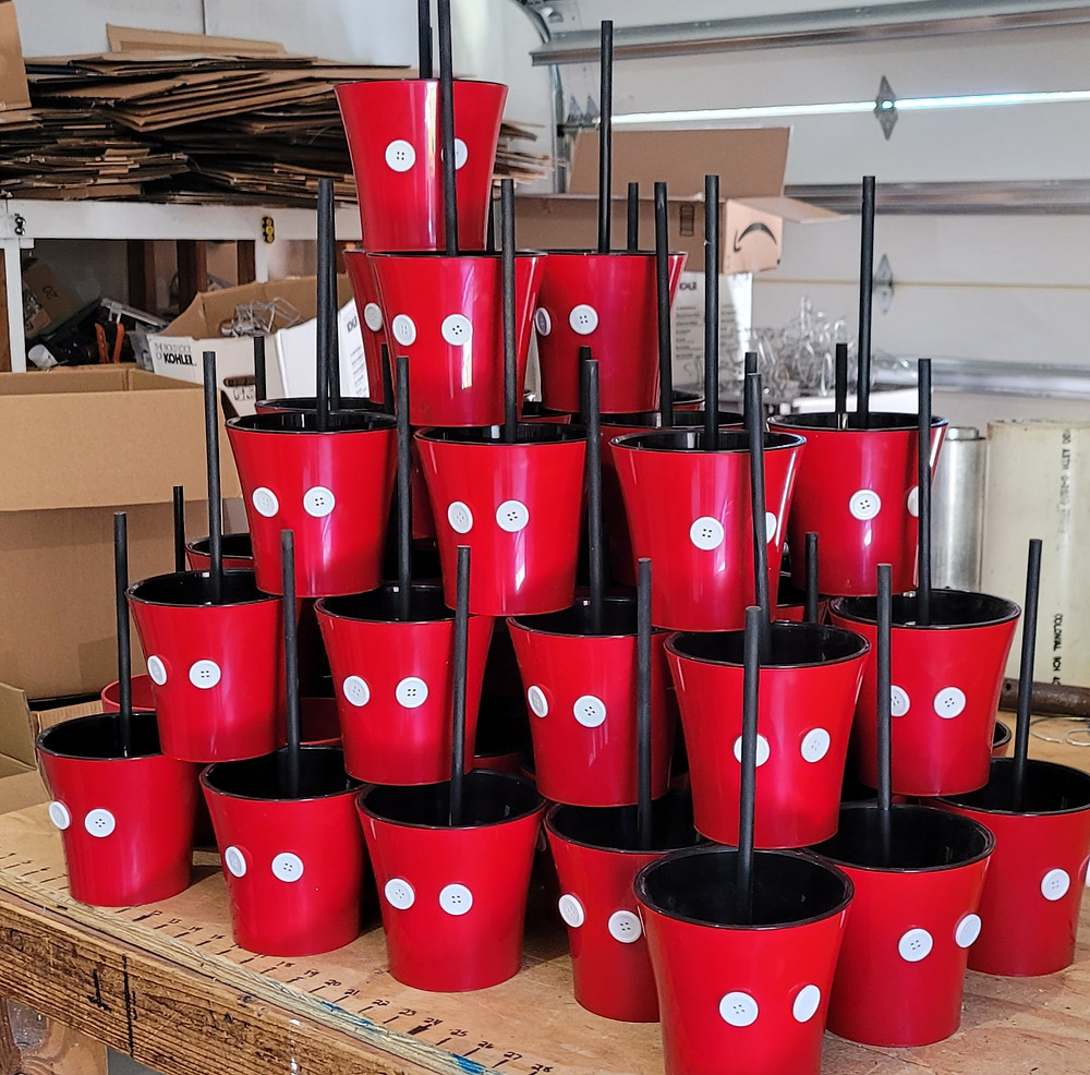 A stack of Mickey Head planter pots in a triangle that are being transformed into the Mickey Head planter pot.