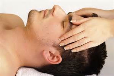 Face and scalp masage. male subject being given aface and head massage , hands are on temples