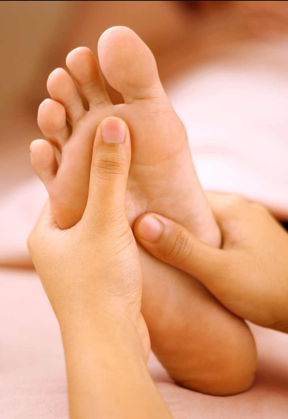The sole of a foot being massaged using the thumbs of both of the therapists hands