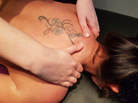 Neck & Shoulder Massage. Hands massaging shoulders of female subject laying face down.