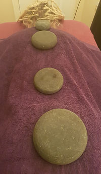 a person lying on the couch face down with a towel over them an four large basalt stones placed on her back. These are left there whilst the massage is continued on the legs.
