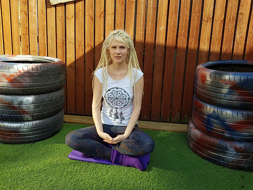 Susan Newman owner of Optimise Therapies sitting crossed legged in meditation pose infront ofa wooden fence and sitting on grass