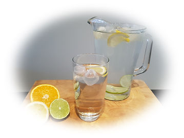 Aftercare. jug and glass of water both with ice and fruit floating, with orange, lemon and lime halves all on a wooden chopping board