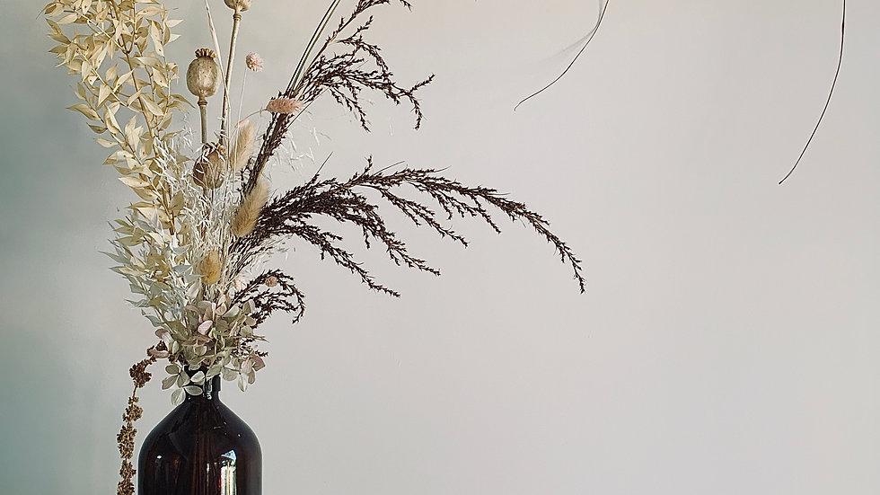 Everlasting arrangement in amber glass bottle