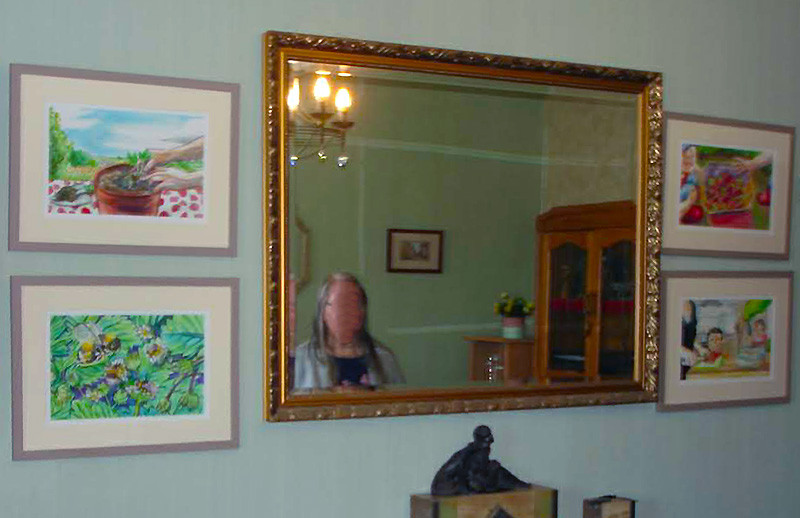 A large mirror with four framed prints around it featuring the life stages of strawberries.