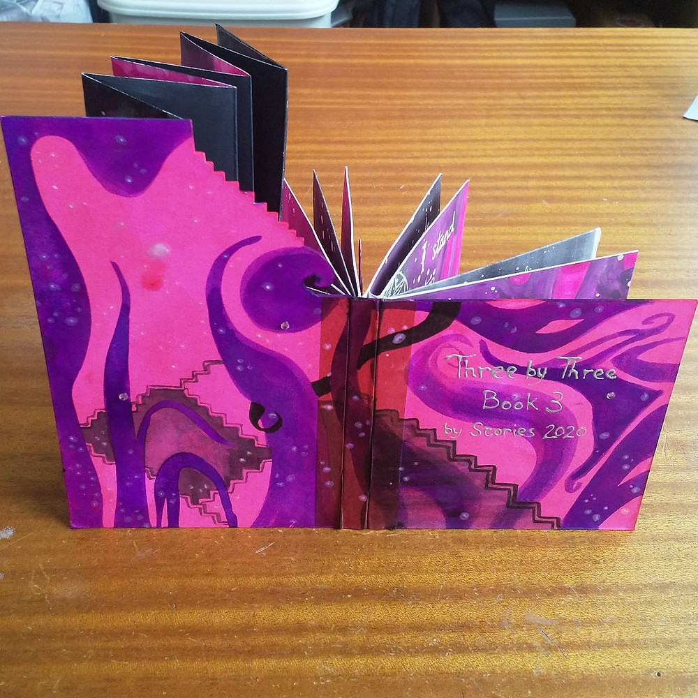 Artist book in pink and purple hues with intricately folded pages.