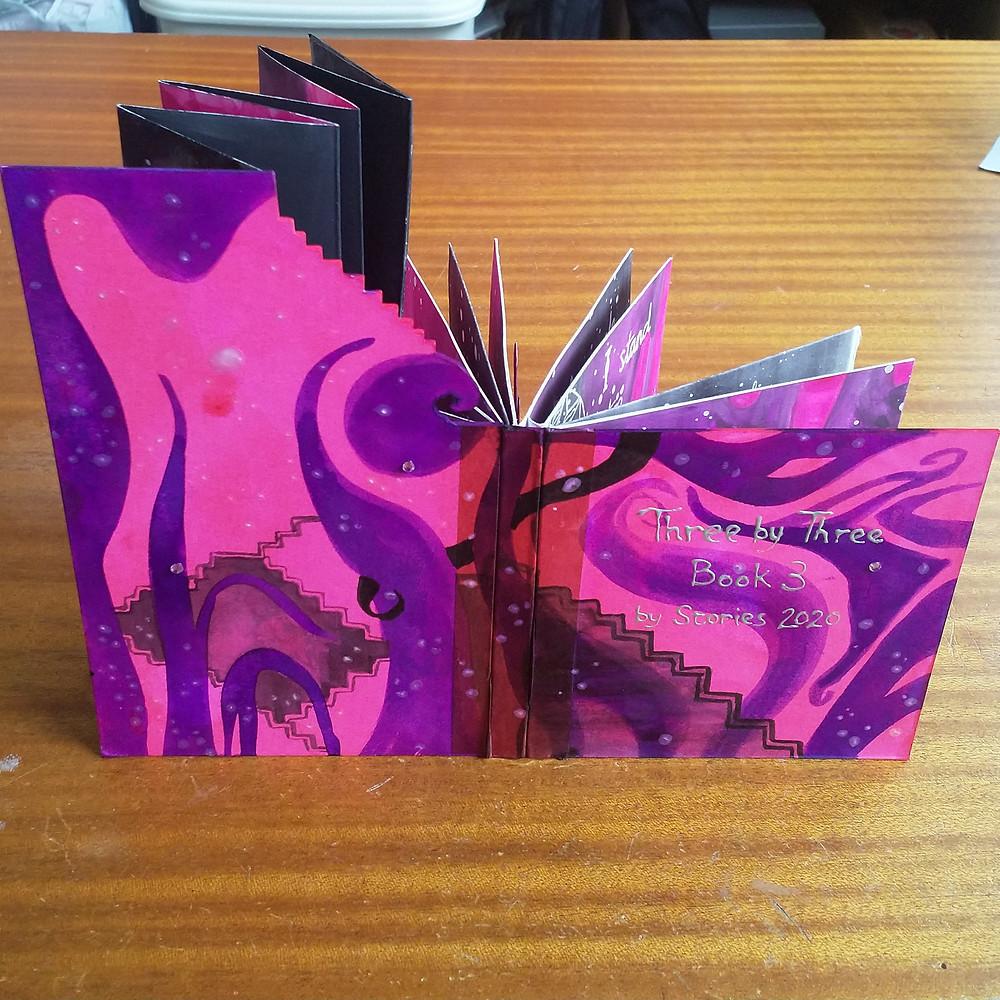 Livre d'art en roses et violets aux plis en escaliers.