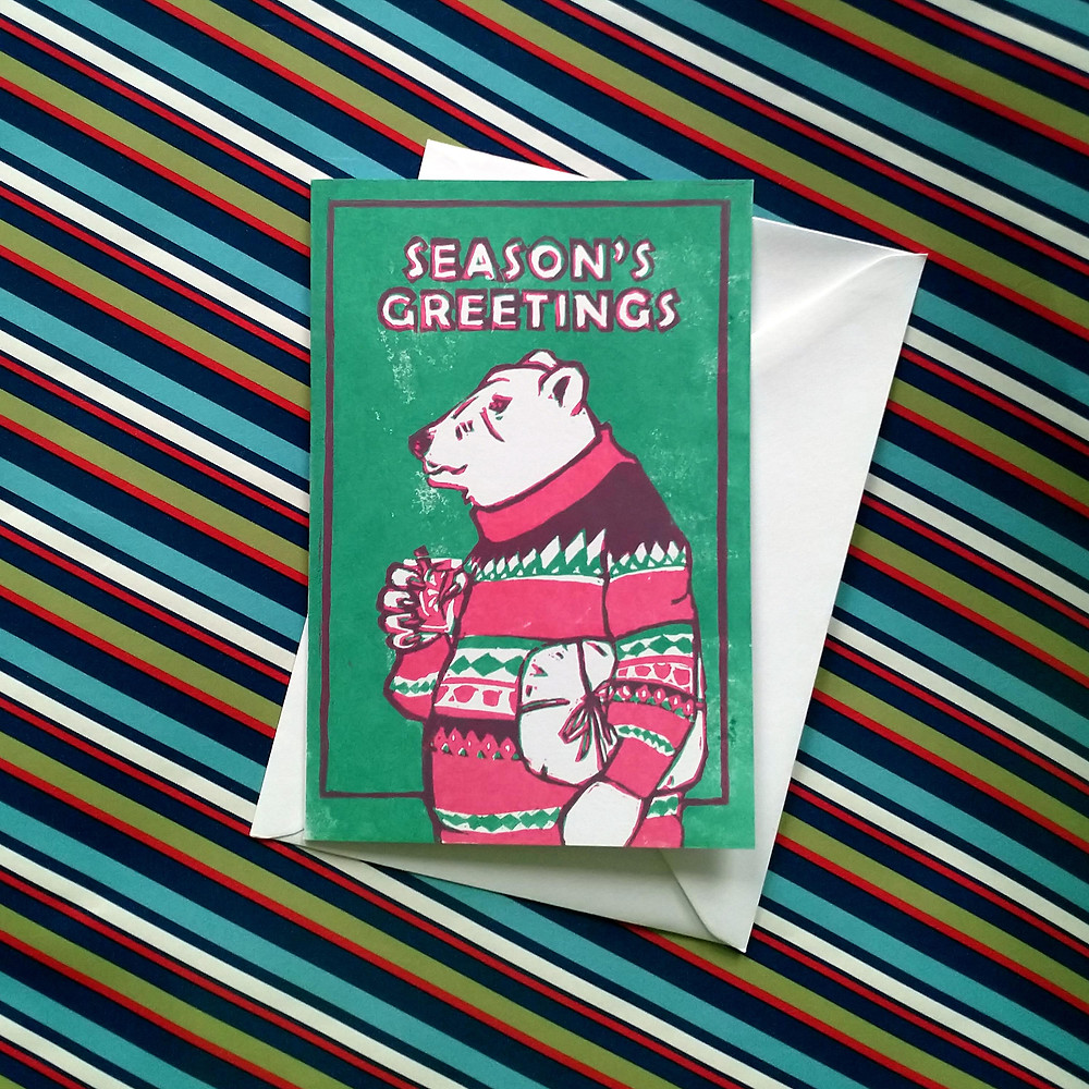 "Christmas card saying ""Season's Greetings"" featuring a Polar Bear in a Patterned Jumper"