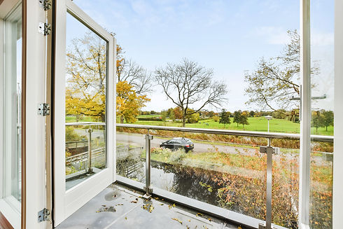 wet-balcony-with-opened-window-glass-fence-viewing-road-with-car-green-fields-rural-land.j