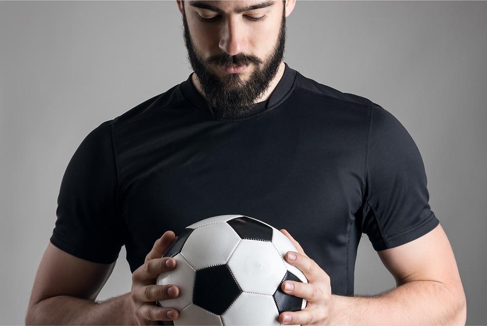 A man examining a soccer ball as a metaphor for testicular cancer
