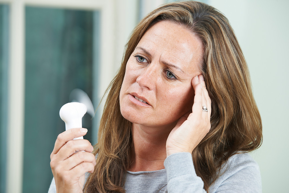A woman using a fan to cool down from a hot flush due to menopause