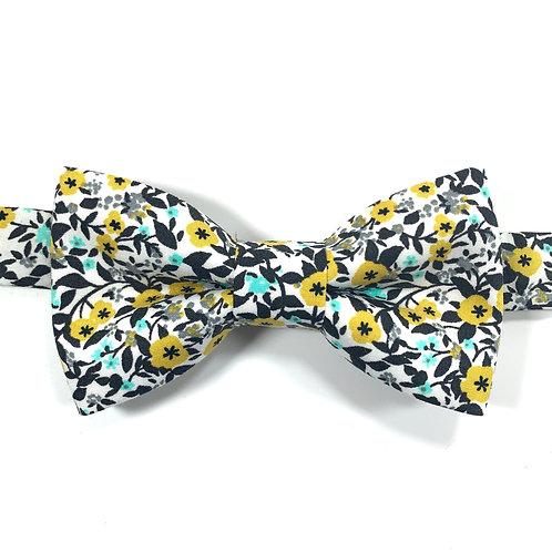 Noeud papillon blanc avec motifs de fleurs jaune et bleu.