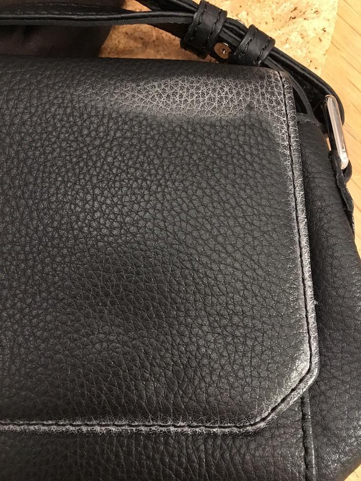 Sort lædertaske med mug skjolder før behandling med æteriske olier