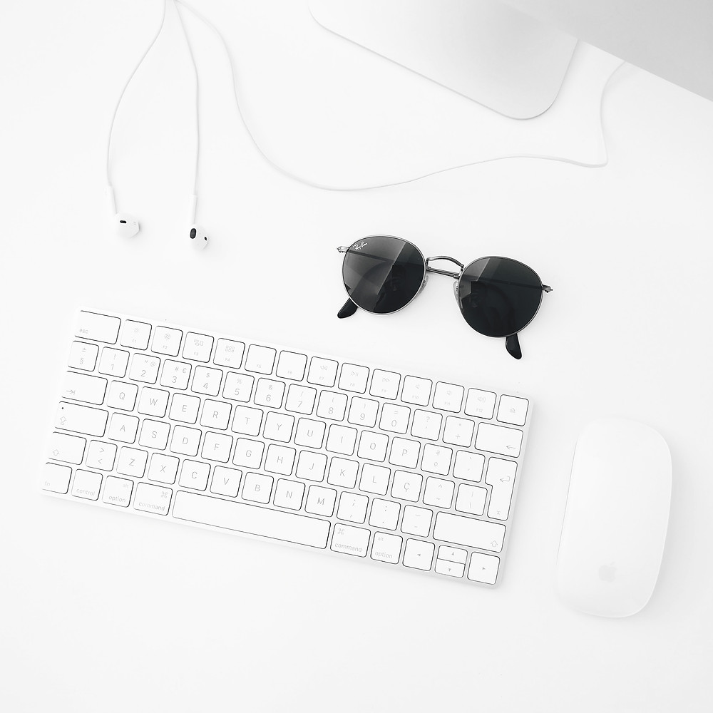 Flatlay with white keyboard, mouse and headphones with black sunglasses. Social media inspiration.