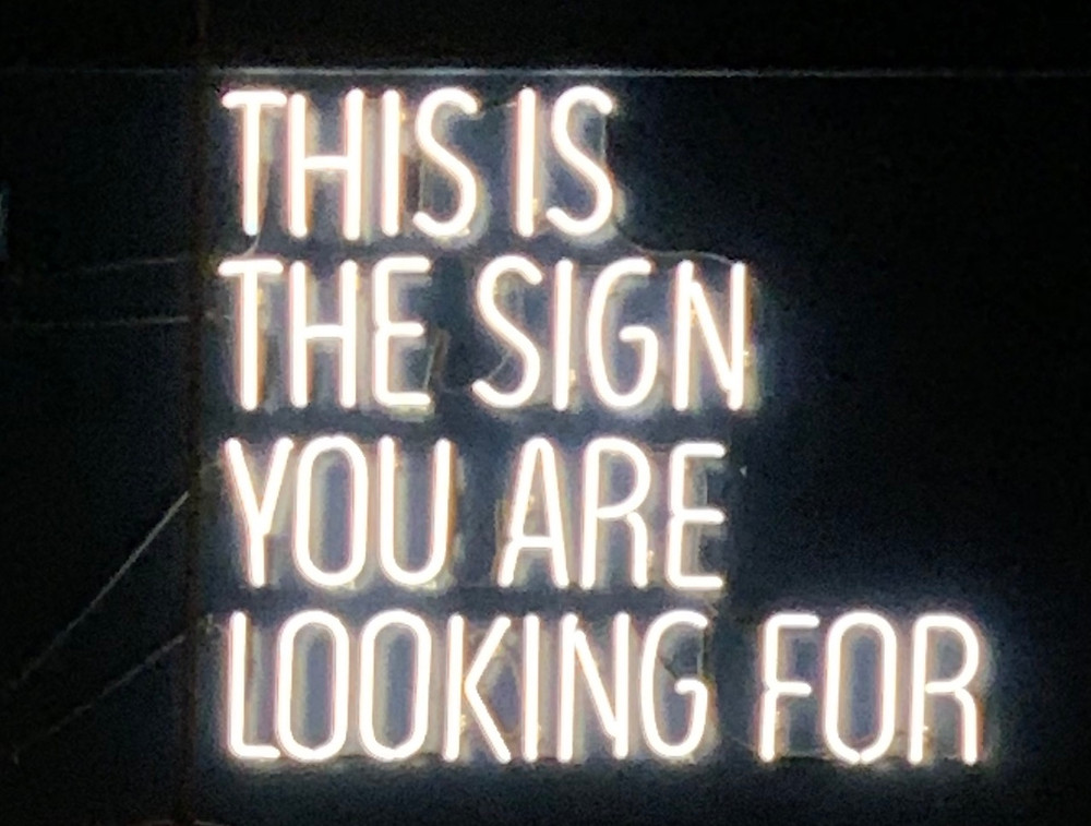 "White neon sign on black background reading, ""This is the sign you are looking for."""