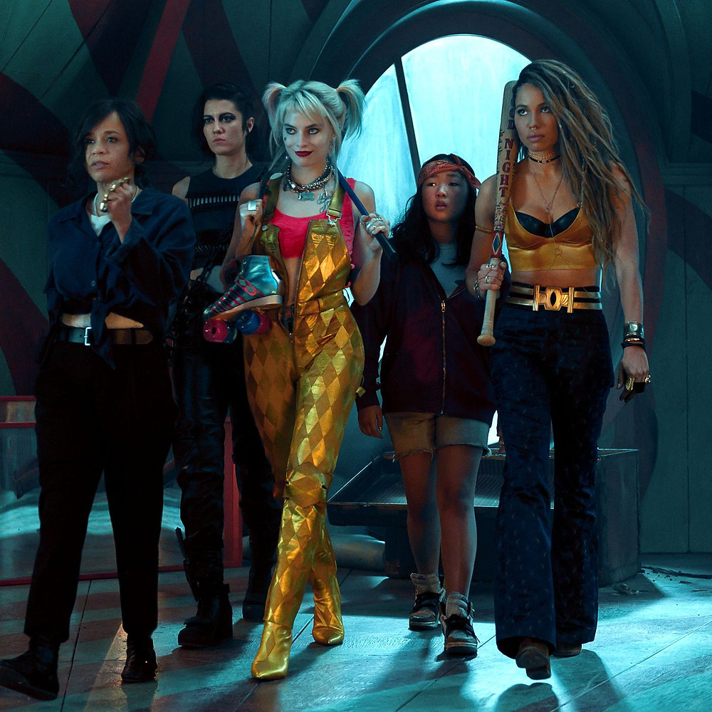 The five characters in Birds of Prey in a dark room.  They are backlit from a large broken round window.  All five are armed and striding purposefully as they look toward their right.