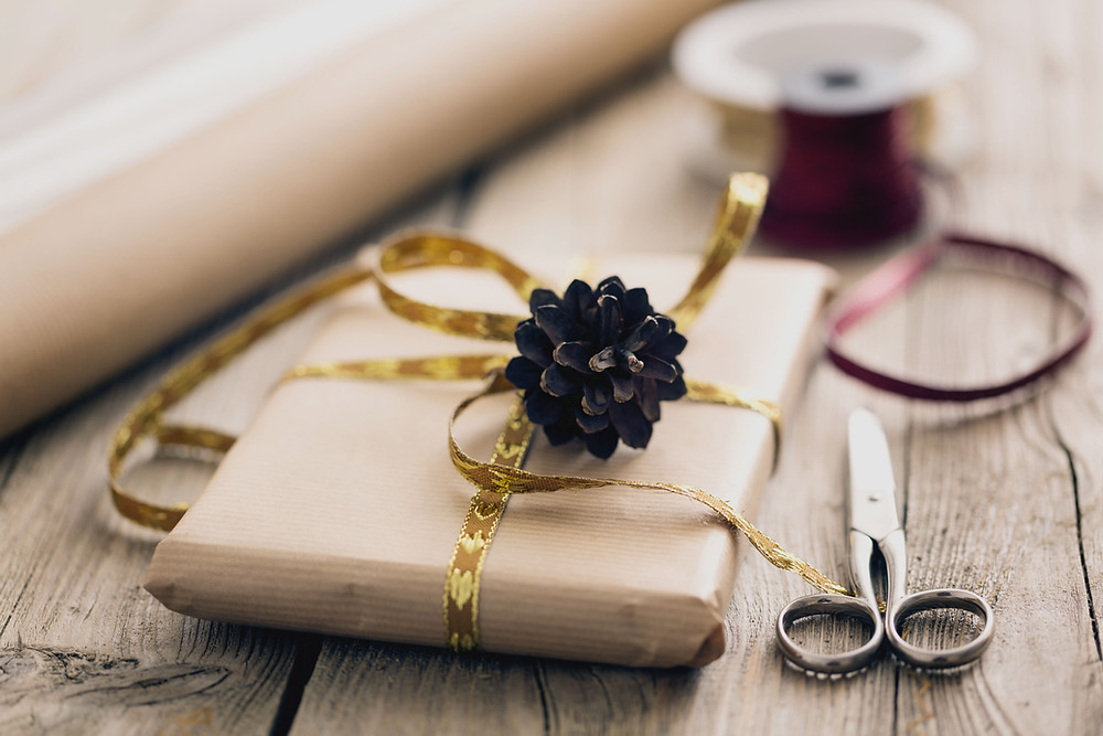 Gift wrapped in brown paper with a gold ribbon