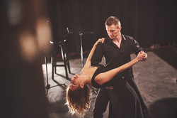 skillful-dancers-performing-in-the-dark-room-under-6R2AWBT
