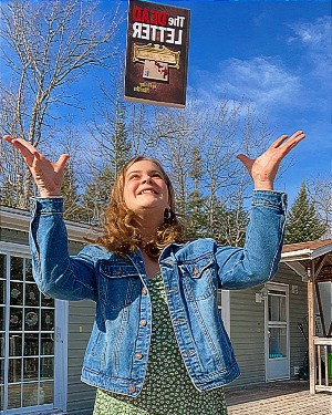 """Youth Ambassador Savannah Ferris throwing the book """"The Dead Letter"""" in the air"""