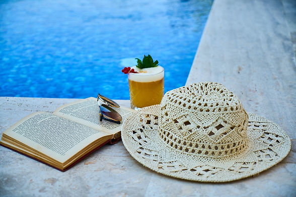 beige-straw-hat-book-sunglasses-and-drin