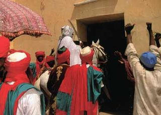 As the Emir enters his palace, his subjects race forward to salute him, raising arms with closed fists in a show of appreciation for their leader. Supreme head of the ruling dynasty, he holds the highest position of traditional power for both Hausa and Fulani communities of the Katsina emirate.