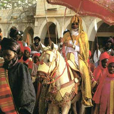 Wearing a gold cloak over a white robe and a turban that signal religious piety, the Emir, proceeds behind members of the aristocracy, and is surrounded by palace attendants in red turbans.