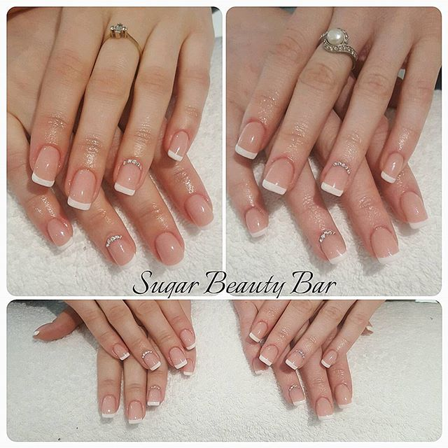 Matching sets of french acrylic extensions for two sisters with a bit of Swarovski bling