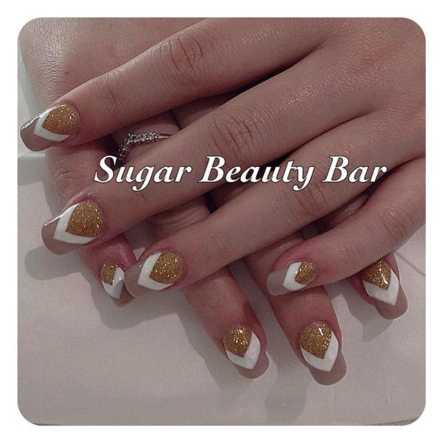 Square tapered acrylic extensions with gold glitter, white and nude chevron nail art