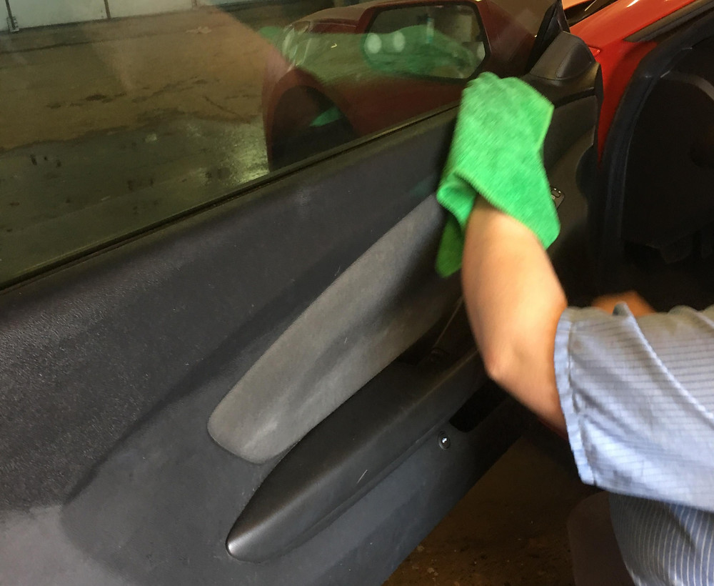 Cleaning the interior of the driver side door with a green cloth.