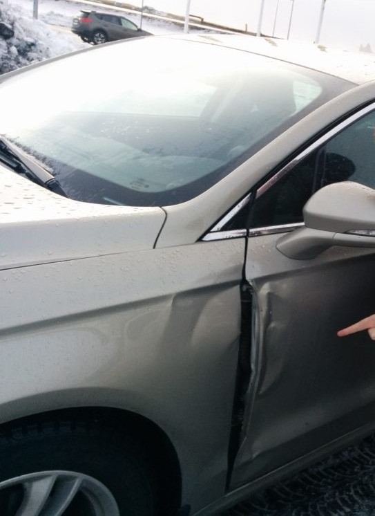 Gray Car with dent damage on driver side door.