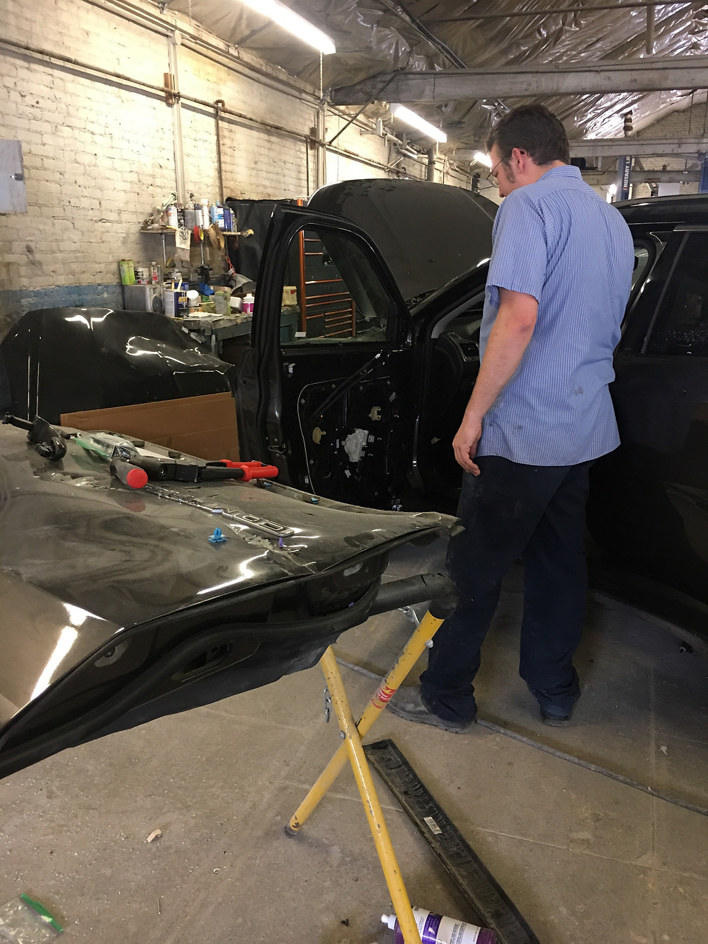 Vehicle doors removed for replacement. Technician is completing the repairs