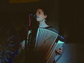 Emma Berkey playing accordion on stage and singing into a microphone. The accordion bellows are open and Emma's eyes are closed.  Photo by Morgan Orion.