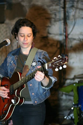 Photo of Emma playing a a wooden hollow body electric guitar. She is looking down at the neck of the guitar and is wearing a jean jacket.