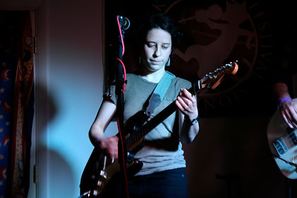 Emma Berkey is playing electric guitar on stage, and her gaze is towards the guitar neck.  Photo by Morgan Orion.