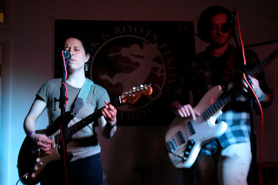 Emma is singing into a microphone with her eyes cosedand playin electric guitar. In the background off to her side is Rob playing bass slightly in the shadow.