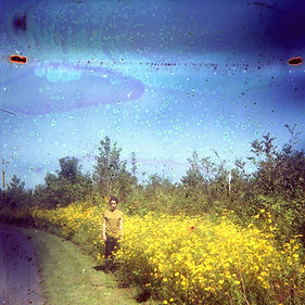 This photo was taken at Shelby Park in Nashville, TN, where Emma is standing off in the distance wearing a yellow shirt. She is off the side of a path next to a field of yellow flowers. The camera film was soaked in lemonade, and is intentionally damaged looking. There are spots and color stains throughout the picture. The top half of the photo is the blue sky.  Photo by Heather Allen.