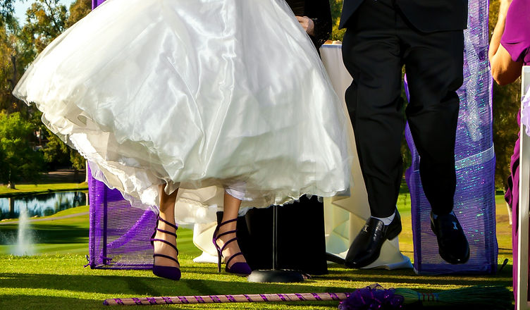 A%20bride%20and%20groom%20jump%20the%20broom%20in%20their%20wedding%20ceremony._edited.jpg