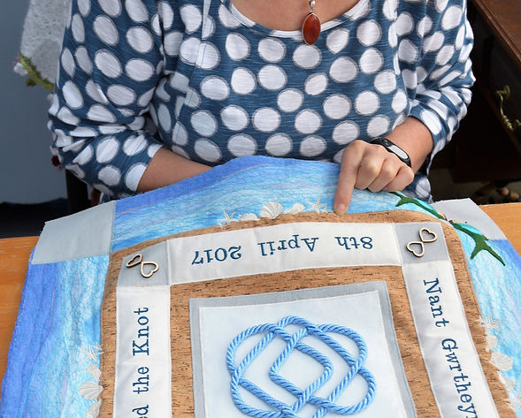 Texitle artist hand sewing pearls on to a wedding wall hanging
