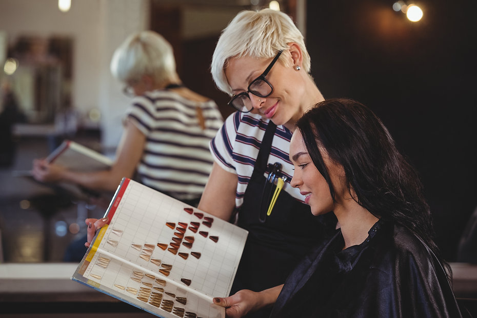 Woman selecting a hair color with stylis
