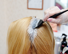 The hairdresser uses a brush to apply th