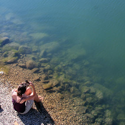 Woman sitting by a still body of water.